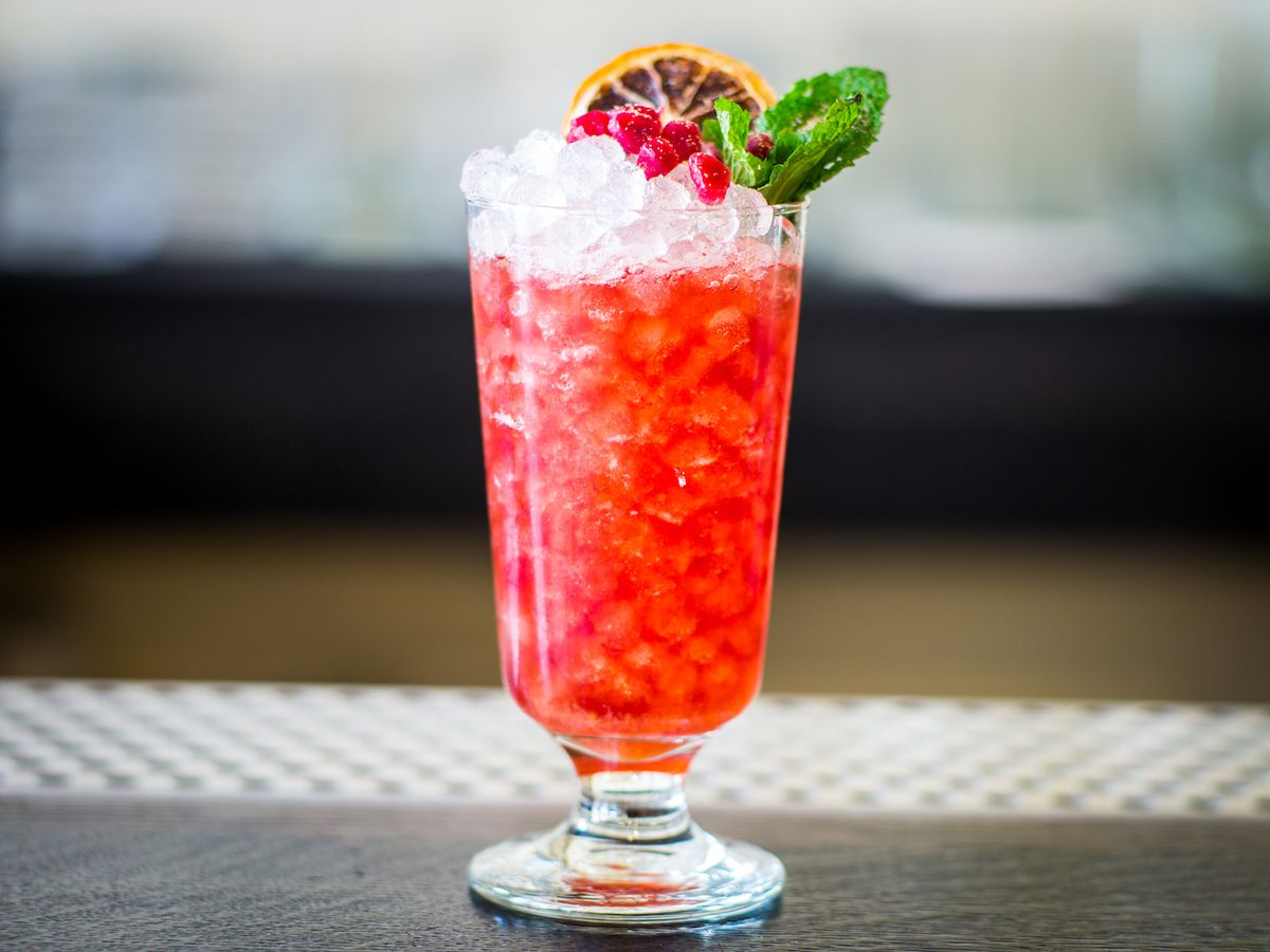 A bright red liquid in a glass filled with crushed ice, with berries, mint, and an orange slice as a garnish on the rim.