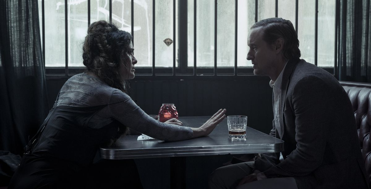 Salma Hayek confronts Owen Wilson by a barred window at a table in a darkened bar in Bliss