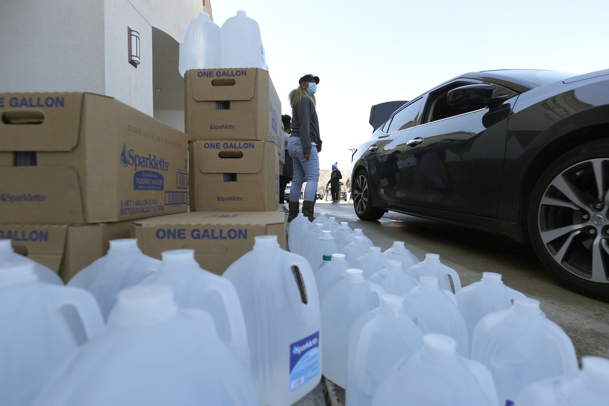 Jugs and cases of water sit on the ground, with volunteers working in the background and a car parked to the right.