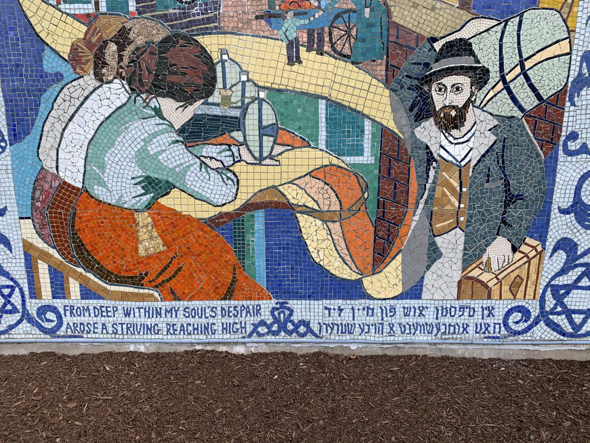 """Three women working in a sweatshop in the """"Fabric of Our Lives"""" mosaic outside the Bernard Horwich Jewish Community Center."""
