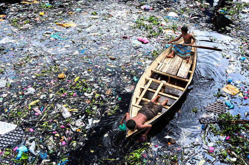 Children collect plastic bottles from a polluted river in Dhaka, Bangladesh.