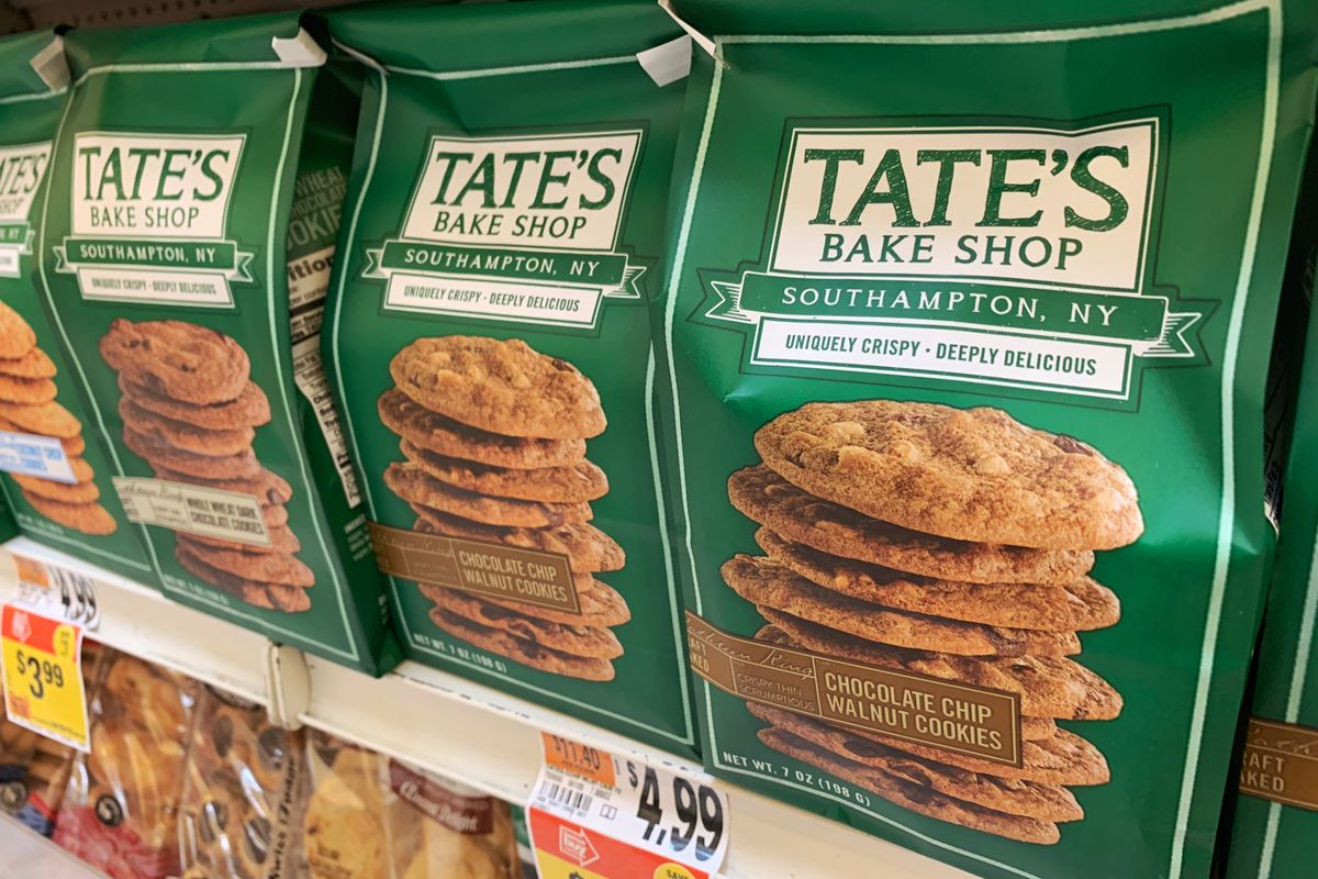 A supermarket shelf stocked with green bags of Tate's Bake Shop cookies
