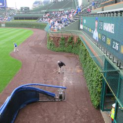 Grounds crew wicking up water off the warning track -