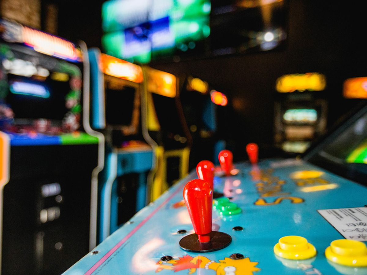 A close up on joysticks on a video game with more games in the background
