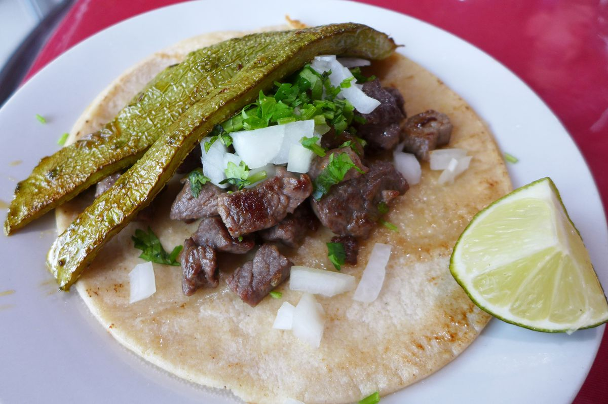 On top of a flat tortilla are strips of both steak and cactus, which has been skinned and despined...