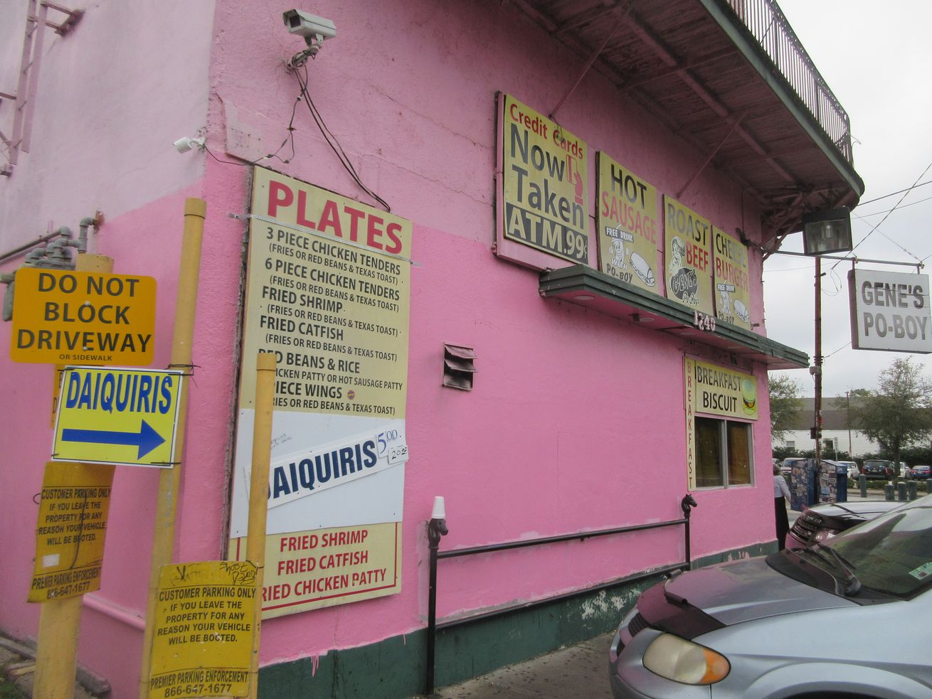 Several yellow signs advertising daiquiris and plate lunches are affixed to a bright-pink building.