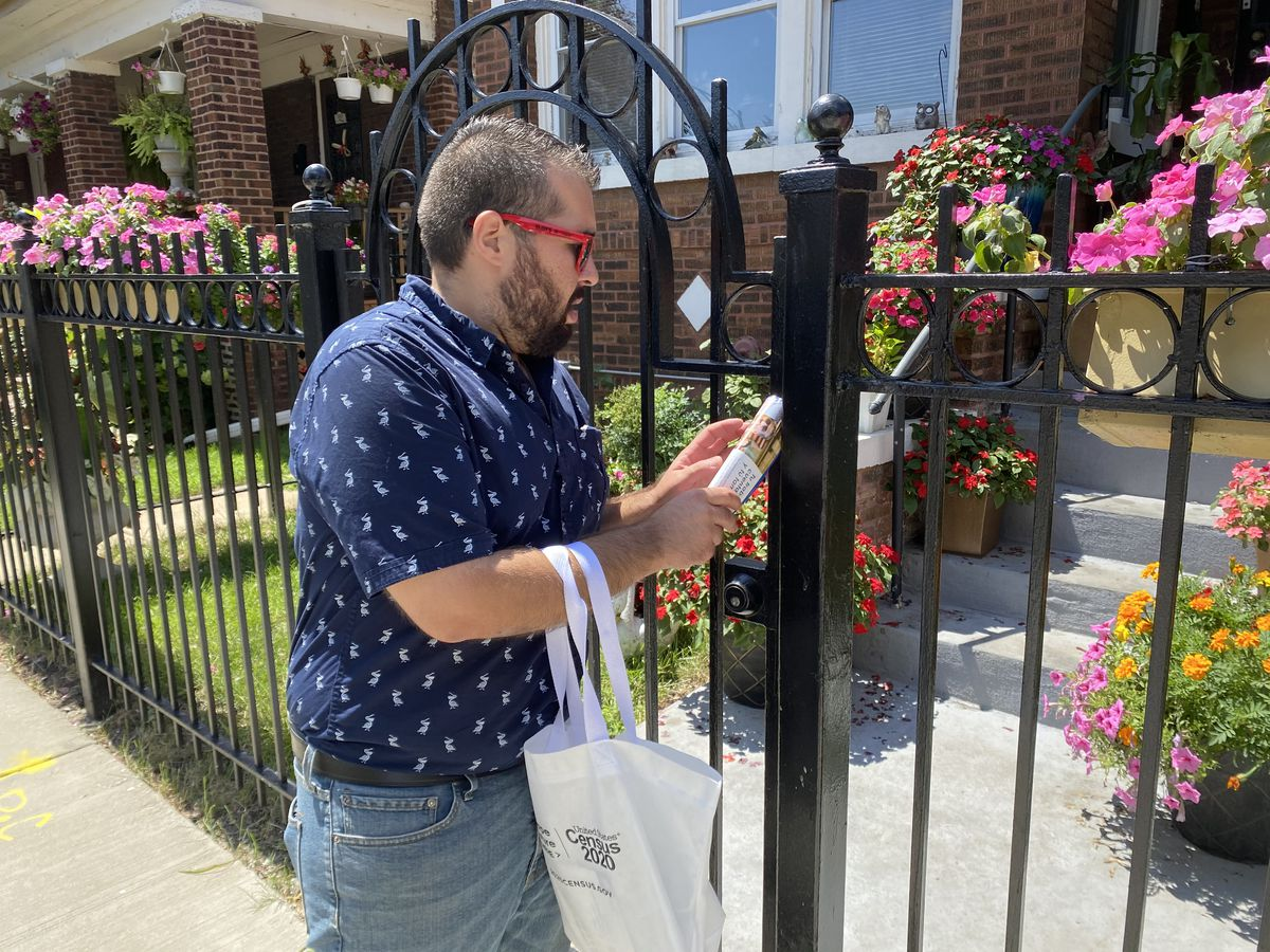 Angel Lorenz, volunteer with the Southwest Organizing Project, leaves census flier on an iron-rod fence in Chicago Lawn on August 4, 2020.  Manny Ramos/Sun-Times