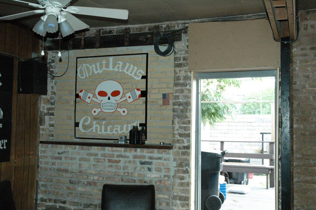 """The Outlaws' logo of a skull and crossed pistons — known as """"Charlie"""" — on the wall of the North Side clubhouse before the building was recently sold."""