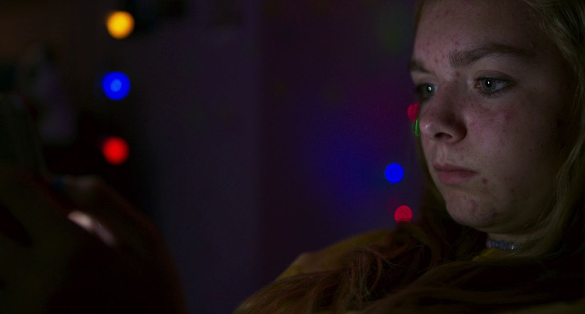 an eighth-grade blond girl with acne sits in the darkness in her room lit by her phone and several Christmas lights