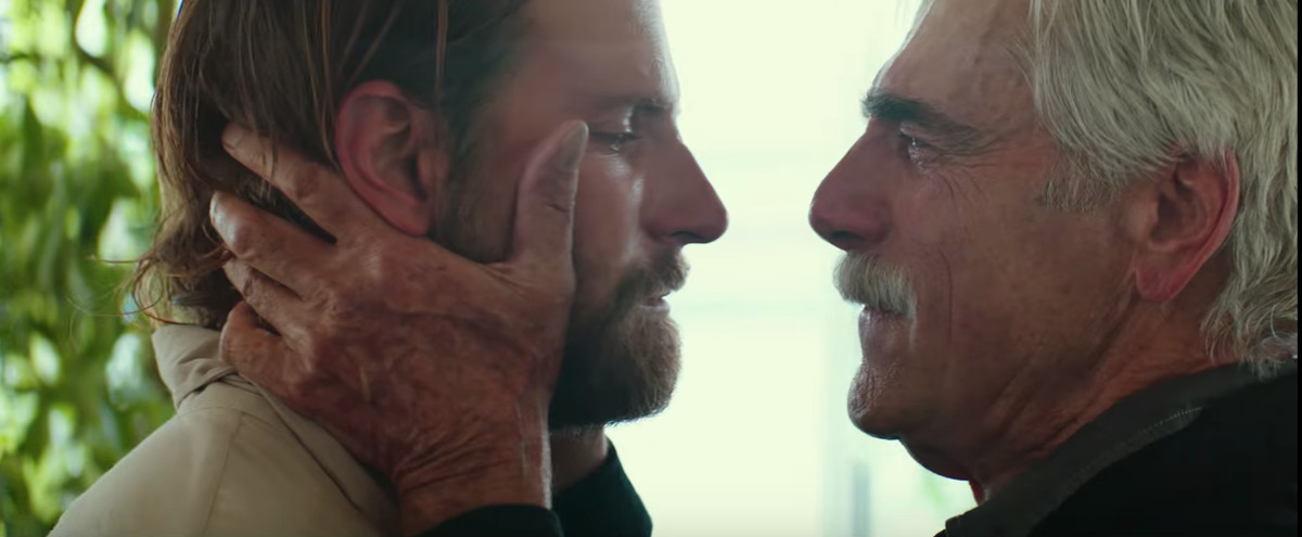 Sam Elliott holding Bradley Cooper's face