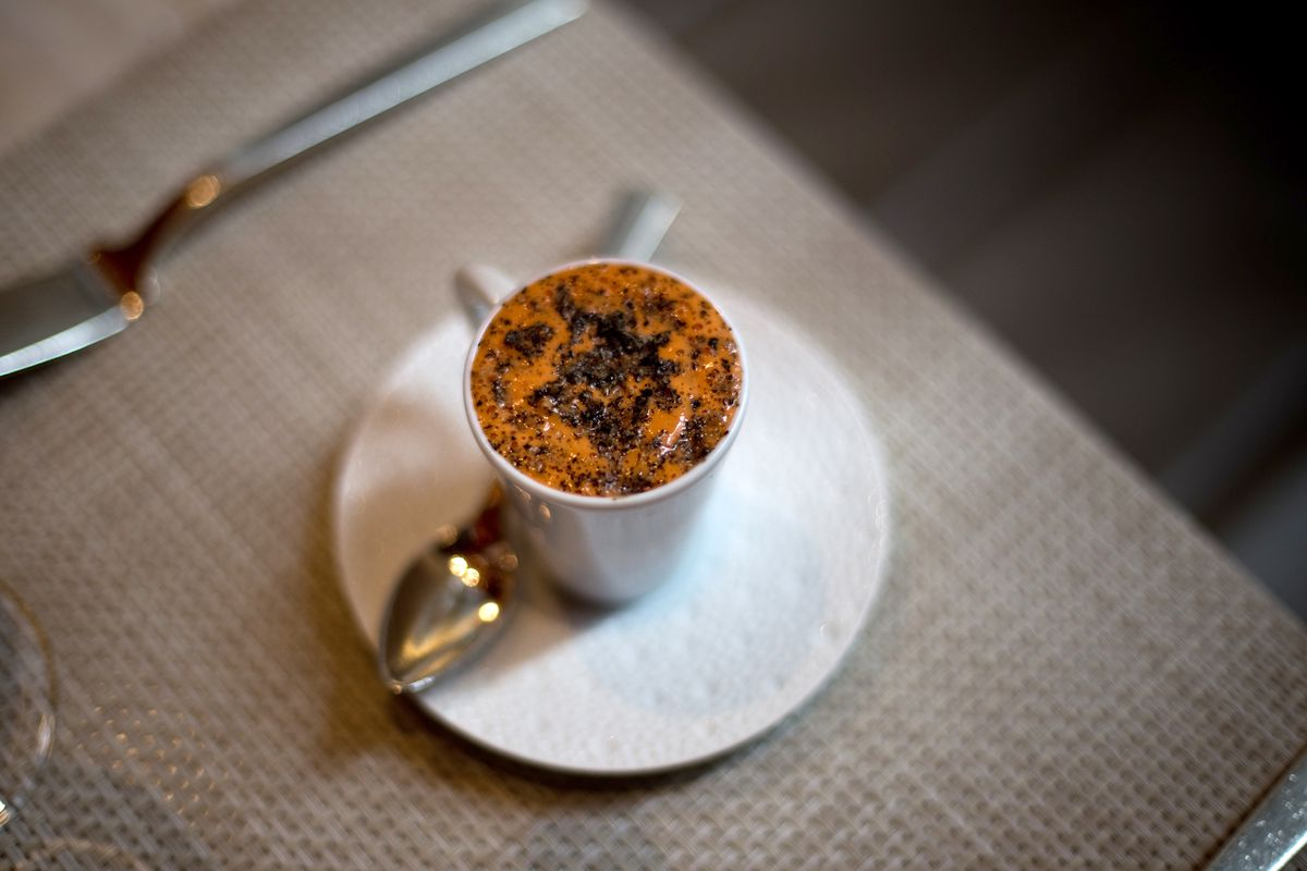 A small demitasse, sitting on a tiny white saucer, contains a dark orange lobster cappuccino