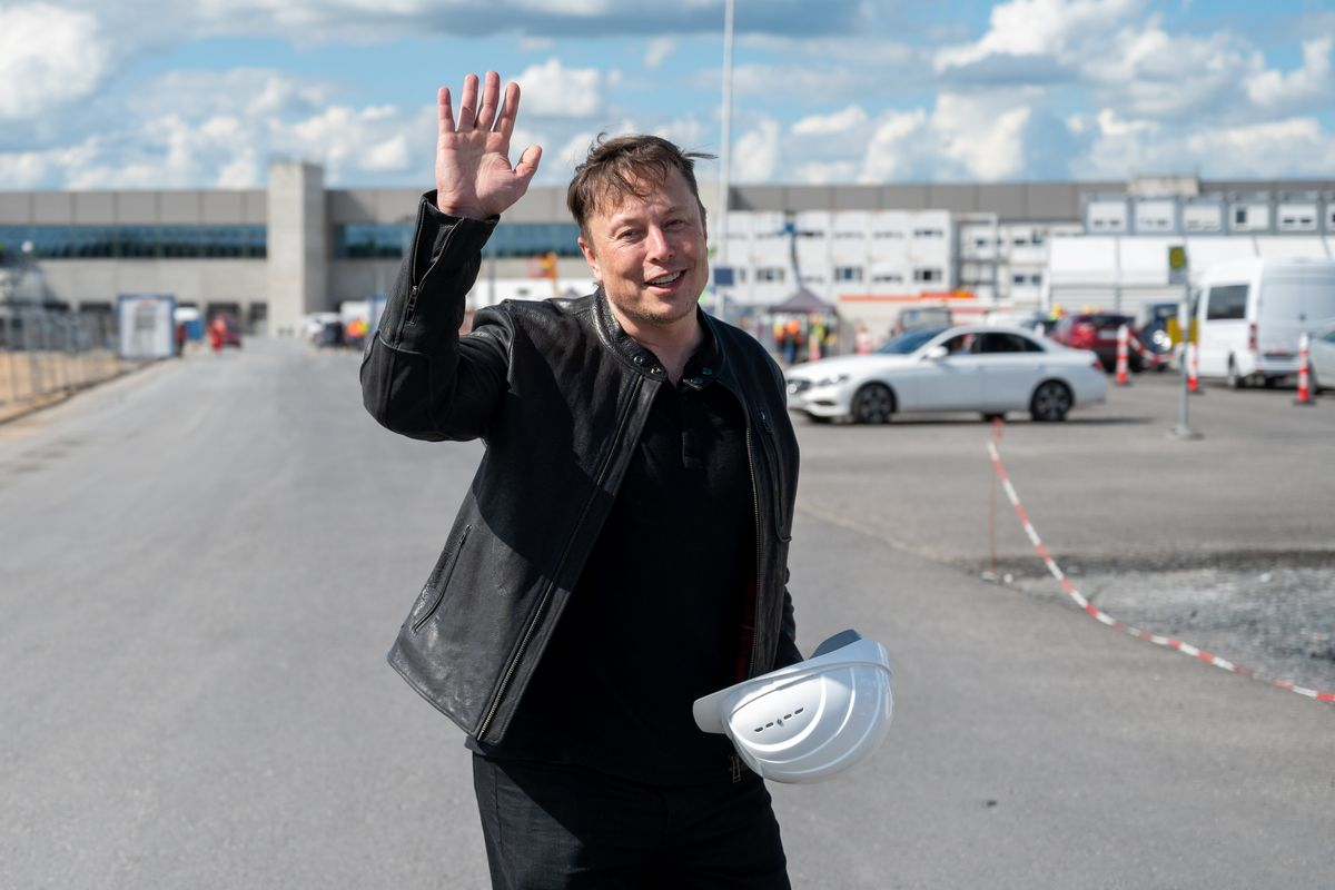 Elon Musk, Tesla CEO, stands on the construction site of the Tesla factory and waves.