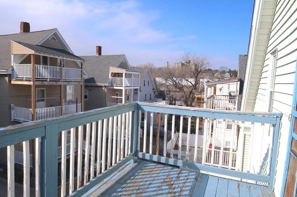 An empty small deck with views of two- and three-story houses.