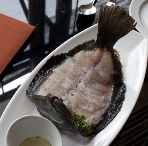 A fish is cut and splayed on a serving dish with a small bowl of dipping sauce nearby