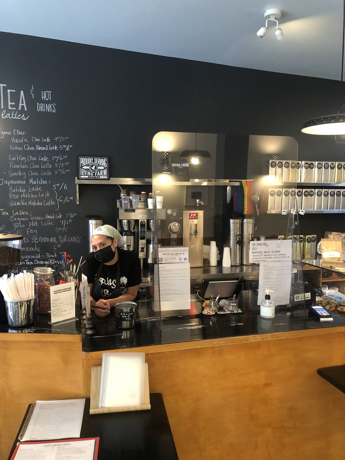 Inside a coffee shop with a counter and a server in a mask standing behind it