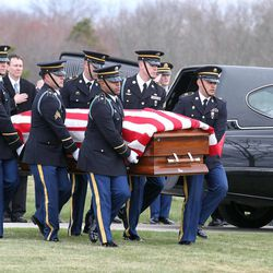 An honor guard carries the remains of Rhode Island National Guardsman Sgt. Dennis Weichel Jr. to his burial plot during funeral services at the state Veterans Cemetery in Exeter, R.I., Monday, April 2, 2012. Weichel Jr., was struck and killed by an armored vehicle March 22 in Afghanistan while saving an Afghan boy. Weichel was posthumously awarded the Bronze Star and NATO Service Medal Afghanistan Campaign Ribbon RI Star.