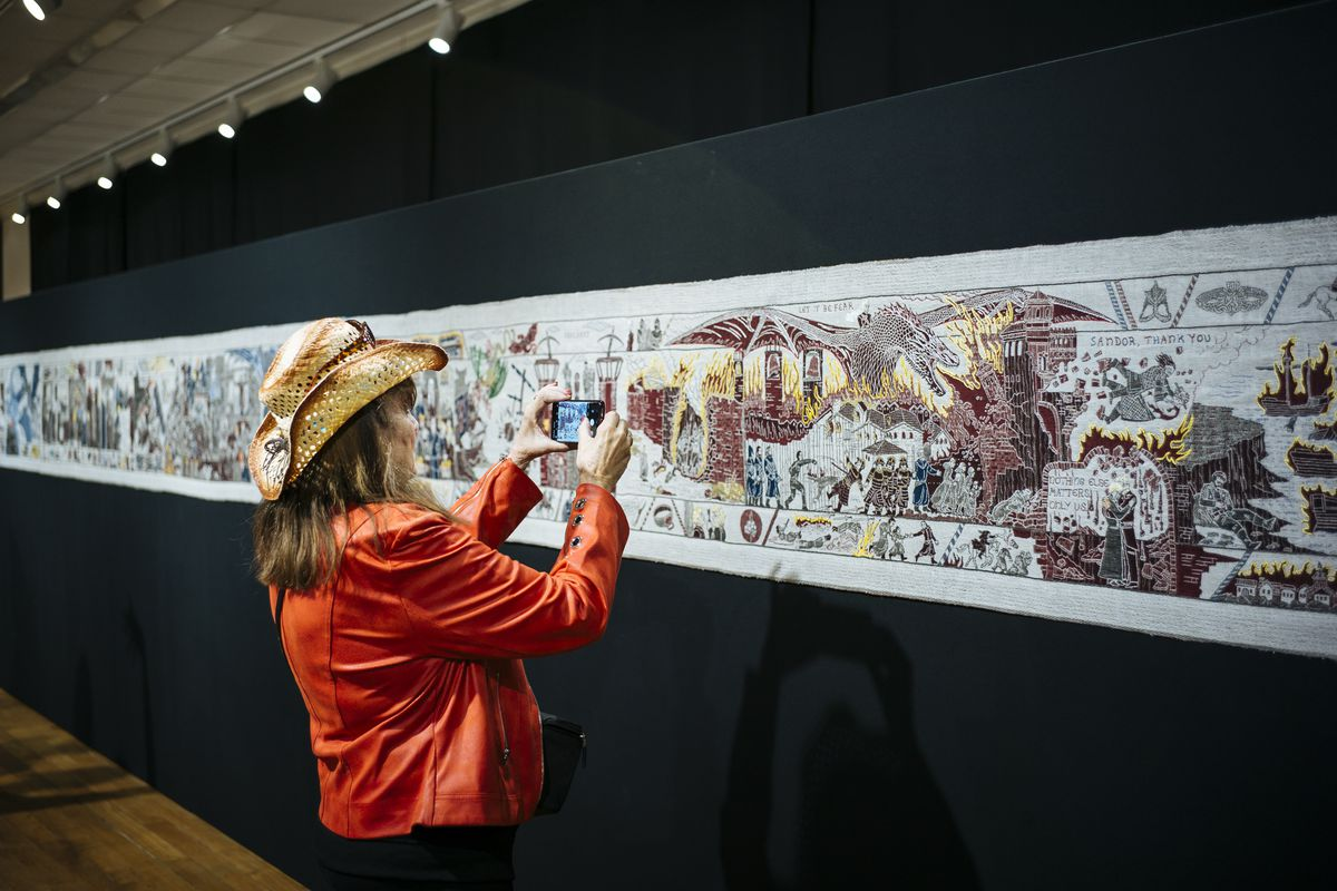 """A woman takes a photo of the """"Game of Thrones"""" tapestry in Bayeux, Normandy, France."""