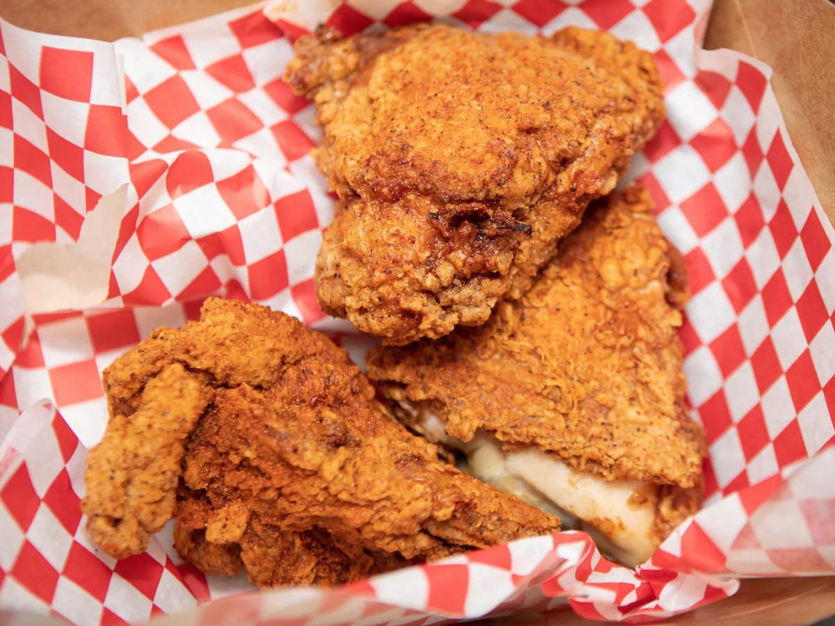 Three pieces of flakey, fried chicken rest in a red-and-white checkered napkin in a takeout basket