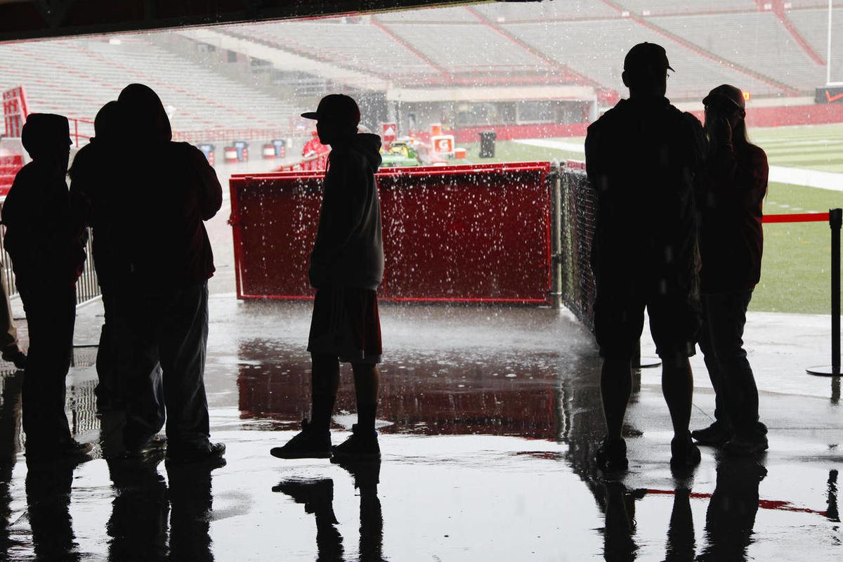Nebraska fans at Memorial Stadium in Lincoln, Neb., take cover from the rain prior to the cancellation of the annual Red-White college football Game, Saturday, April 14, 2012. Nebraska has canceled its spring football game because of heavy rain, hail and