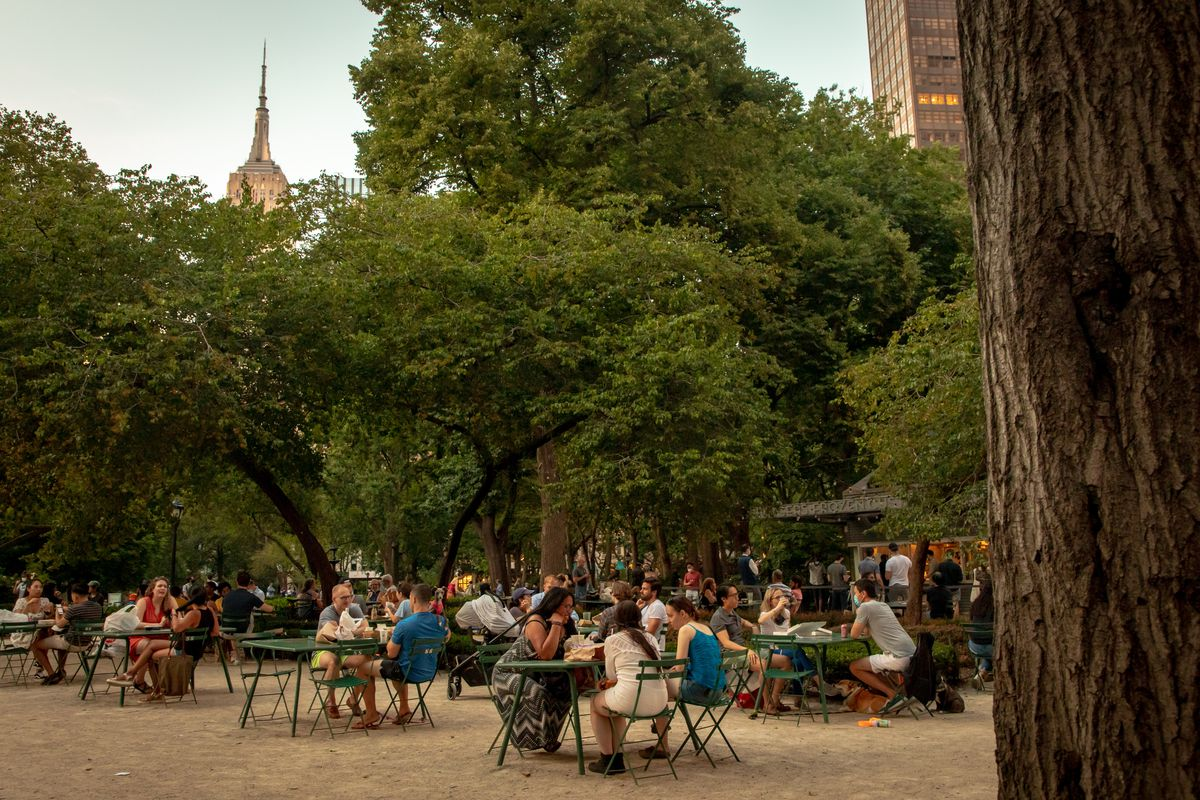 Outdoor diners eat and drink at tables in a park. In the background, trees and skyscrapers are visible.