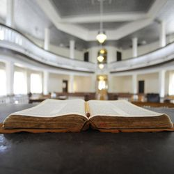 """This July 8, 2015, photo, shows a Bible opened on the judge's desk in the old Monroe County Courthouse in Monroeville, Ala. The building is a centerpiece in the hometown of """"To Kill a Mockingbird"""" author Harper Lee, whose second book """"Go Set a Watchman"""" is set for release July 14, 2015. The courtroom was used as a model for the film adaptation of """"Mockingbird."""""""