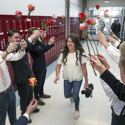 Amanda Jackson is given a rose by members of the Herriman High School boys cross-country and track teams as she arrives at school on Friday, Feb. 14, 2020. The boys decided they didn't want anyone feeling left out on Valentine's Day, so they went to work and raised enough money to buy roses for every girl at the school. The fundraising was so successful the Herriman students had enough roses to share with neighboring Riverton High School, where the flowers were also handed out to female students.