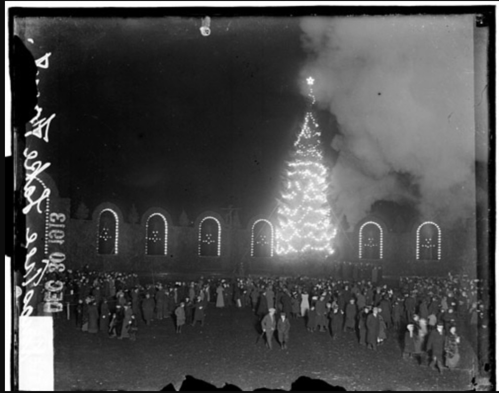 A vintage black and white photo of a crowd near a Christmas tree.