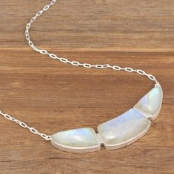"""The iridescent stones set in the <a href=""""http://adornbysarahlewis.com/collections/necklaces/products/crescent-moonstone-necklace"""">Crescent Moonstone Necklace</a> ($298) read as a neutral. Translation: The necklace will go with everything!"""