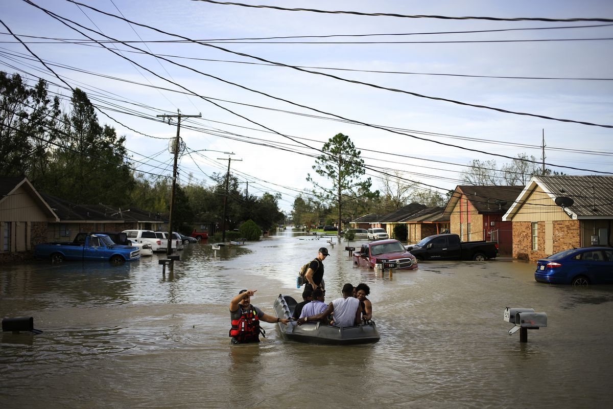 A rescuer in waist-deep water has a hand on a rubber raft holding several people being evacuated from their flooded neighborhood.
