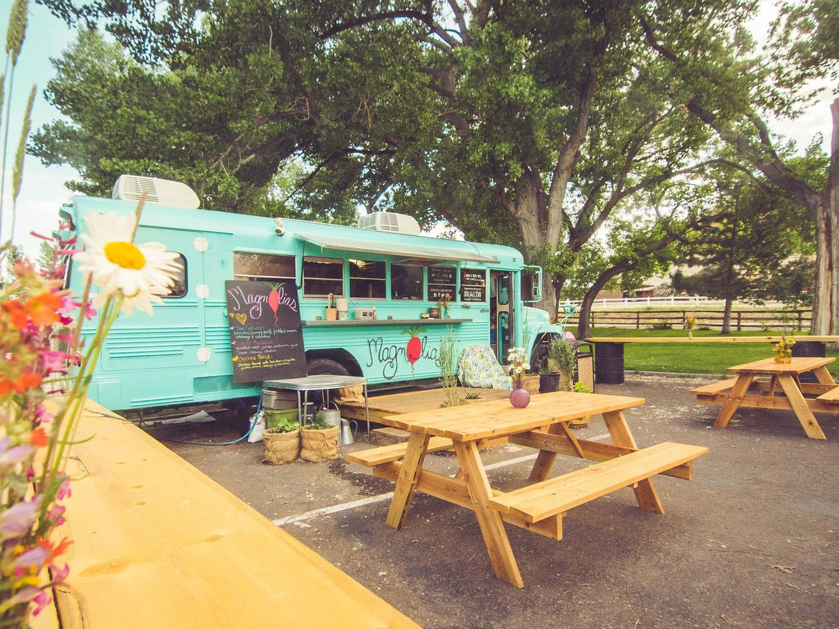 A 1993 aqua colored Chevy Bluebird Bus with picnic tables in front.