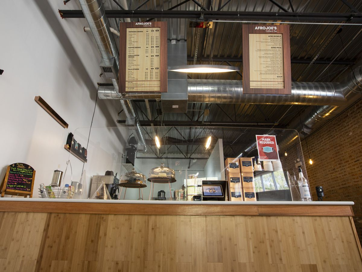 a wooden cafe counter with two menu boards hanging overhead and a glass partition in front of the cash register