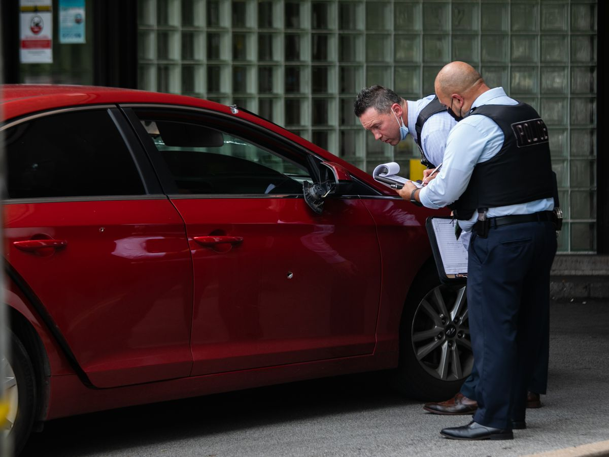 Chicago police officers inspect a car Saturday that was used to take a woman and a child to St. Bernard Hospital for treatment after both were wounded in a shooting in the 6300 block of South Yale Avenue in Englewood.