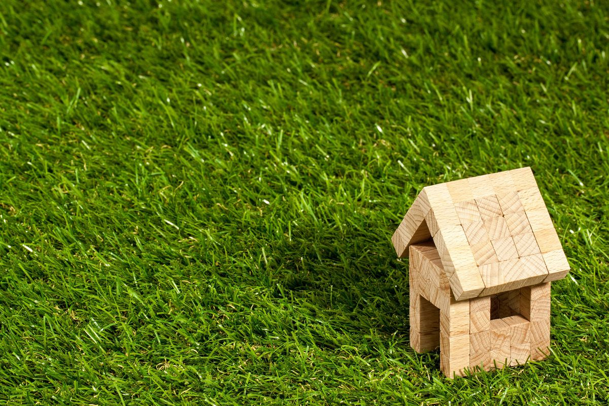 A little wooden house model on a big thing of fake grass