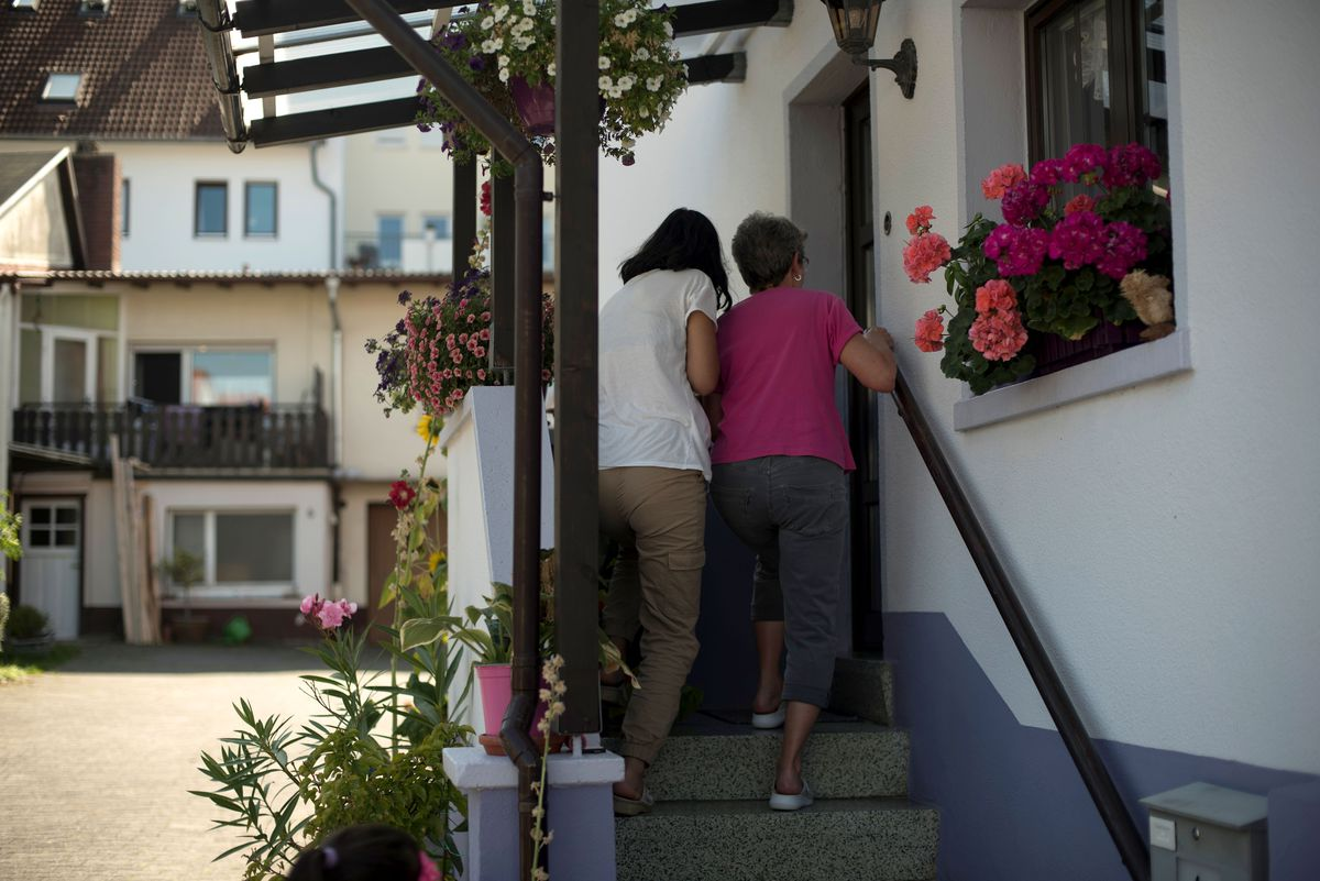 Hind Al Hammoud and her adopted grandmother, Traudelinde Eichhorn, race into Eichhorn's home to find a small trove of photographs on Saturday, Sept. 14, 2019, in Neu-Anspach, Germany. Al Hammoud says she doesn't like most photographs of herself, and was afraid Eichhorn would show unflattering photos to their guests.