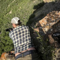 Deseret News photojournalist Spenser Heaps leans over the edge of a cliff, with Hawkwatch International conservation biologist Jordan Herman leaning on his legs for safety, while taking photos at a golden eagle nest site in Tooele County on June 17, 2021.