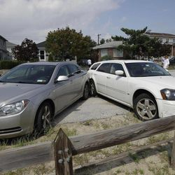 Two cars that collided into each other remain at a 45 degree angle after a possible tornado touched down in the Breezy Point neighborhood in New York, Saturday, Sept. 8, 2012.   A tornado swept out of the sea and hit the beachfront neighborhood in New York City, hurling debris in the air, knocking out power and startling residents who once thought of twisters as a Midwestern phenomenon. Firefighters were still assessing the damage, but no serious injuries were reported and the area affected by the storm appeared small.