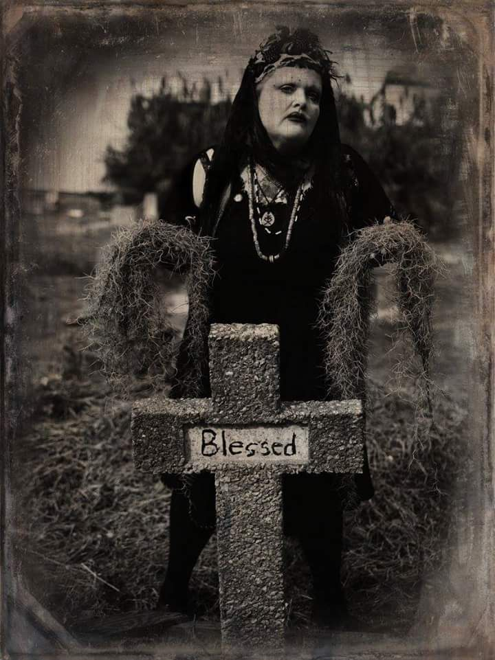 A woman stands behind a gravestone which is shaped like a cross and has the word: blessed written on it. The woman is dressed in a black dress and has multiple necklaces. She is wearing black lipstick.