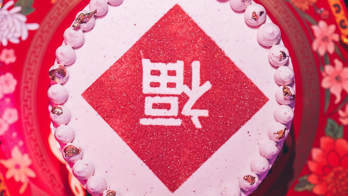 """Pink and red cake with the Chinese character for """"fortune"""" written upside down"""