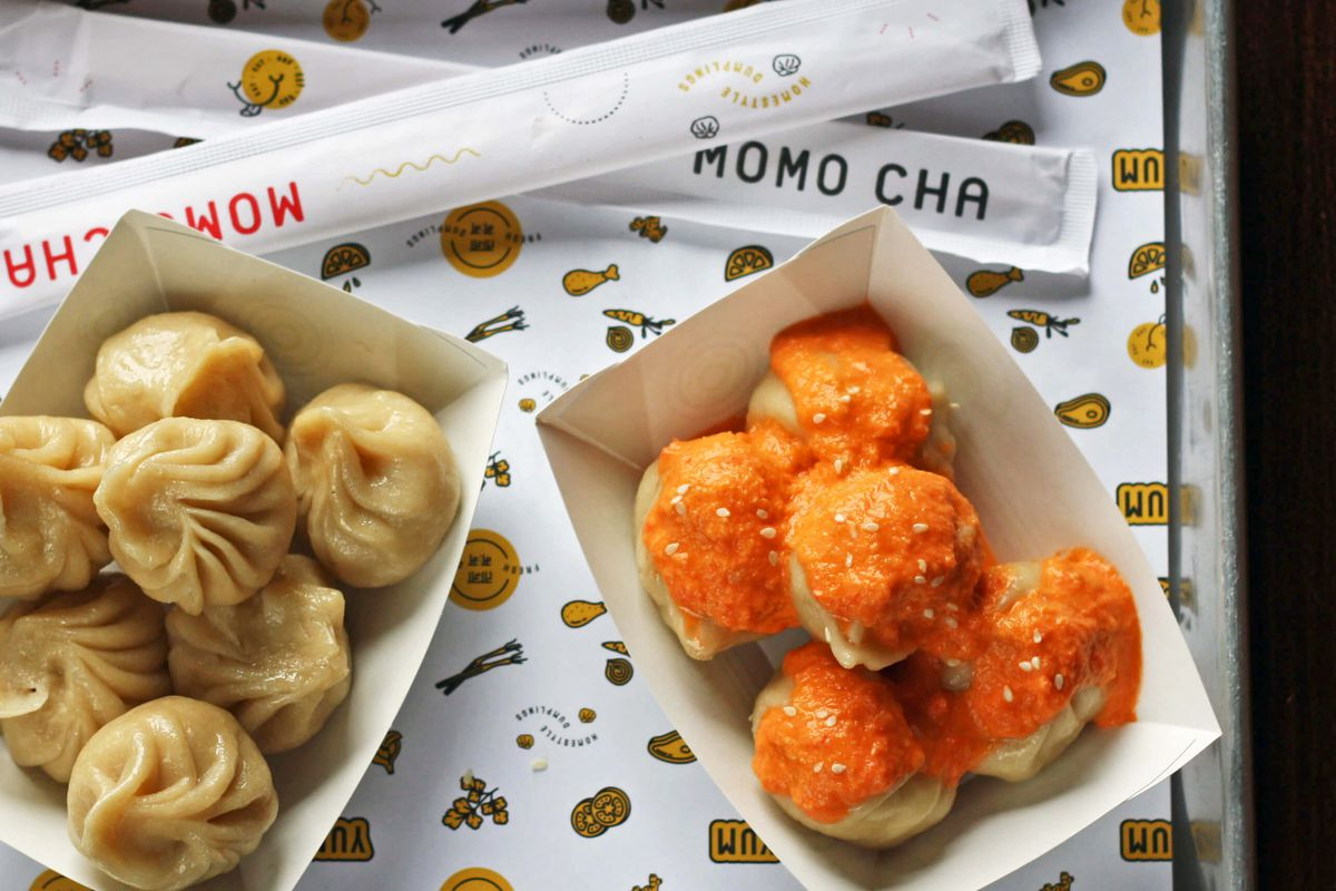 Two boats of steamed momos on a metal tray. One set of momos is topped with a bright orange chutney.
