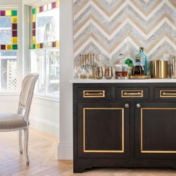 Colorful stone in the chevron backsplash behind the bar picks up the gold accents in the black bar cabinet and the bright tones in the stained-glass windows of the dining nook.