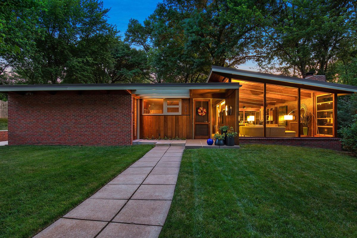 An exterior view of a brick midcentury modern home with its lights on at night.
