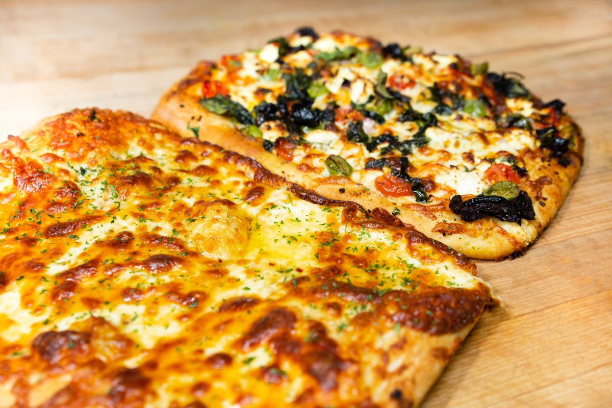 Two pizzas, one with cheese and another with vegetables