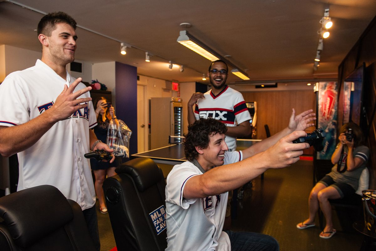 Justin Grimm and Derek Holland of the Texas Rangers react after playing MLB 13: The Show on Playstation 3 at the MLB Fan Cave on June 25, 2013 at Broadway and 4th Street in New York City.