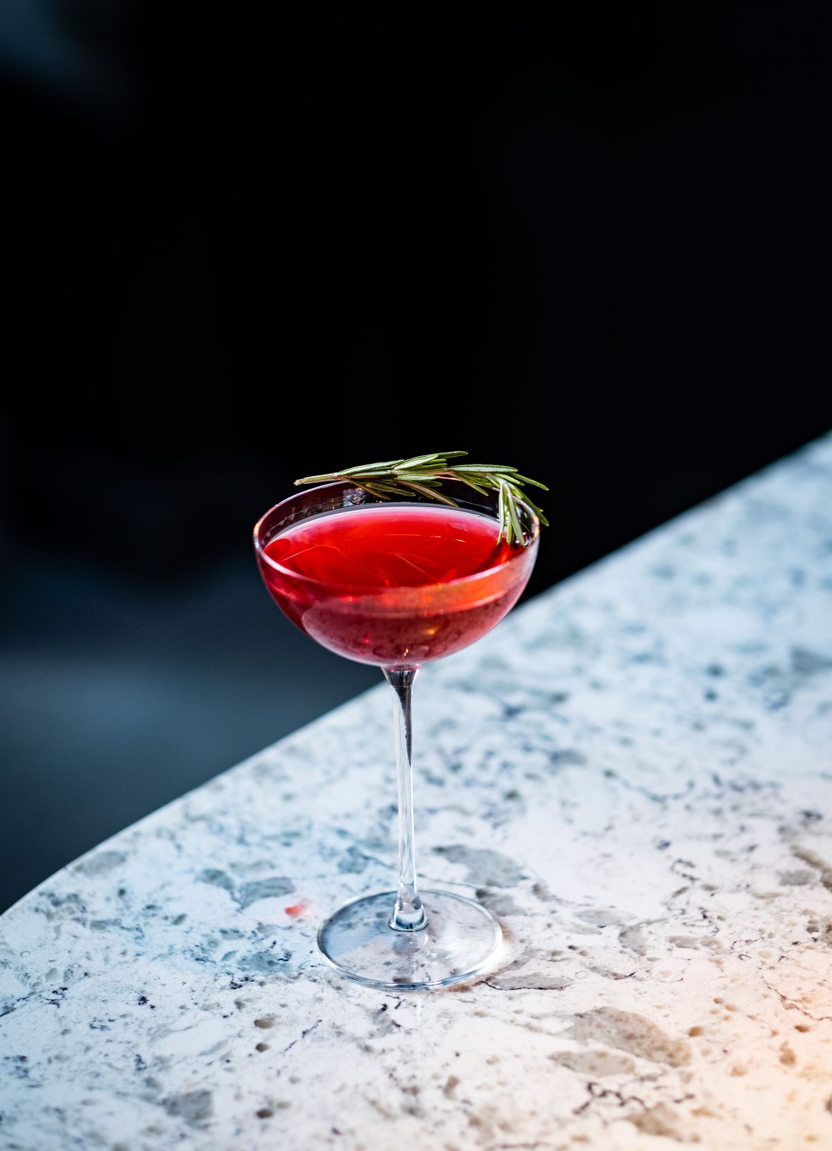 An red cocktail with a sprig of rosemary is served on a marble bar top with a deep blue curtain in the background