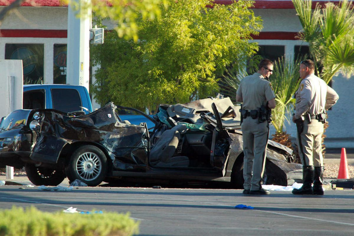 Police officers stands near a vehicle involved in a crash at a bus stop, Thursday, Sept. 13, 2012 in Las Vegas. Police suspect a driver was drunk and speeding Thursday morning when his vehicle went airborne, spun out and plowed into a Las Vegas bus stop,