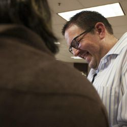 Gregory Enke smiles as he receives his marriage certificate with Ariel Ulloa Gonzalez, left, at the Salt Lake County Clerk's Office in Salt Lake City, Monday, Oct. 6, 2014.