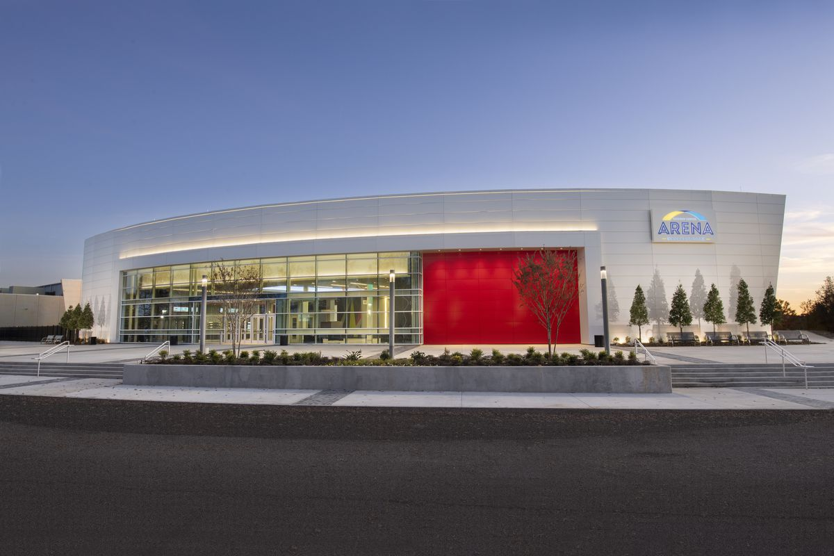 The exterior of a large arena with red walls and glass entrance.