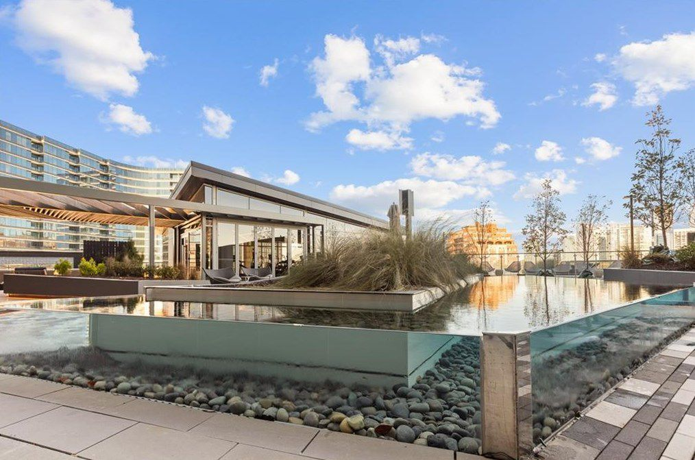 A pond with glass walls around a condo building amenities level.