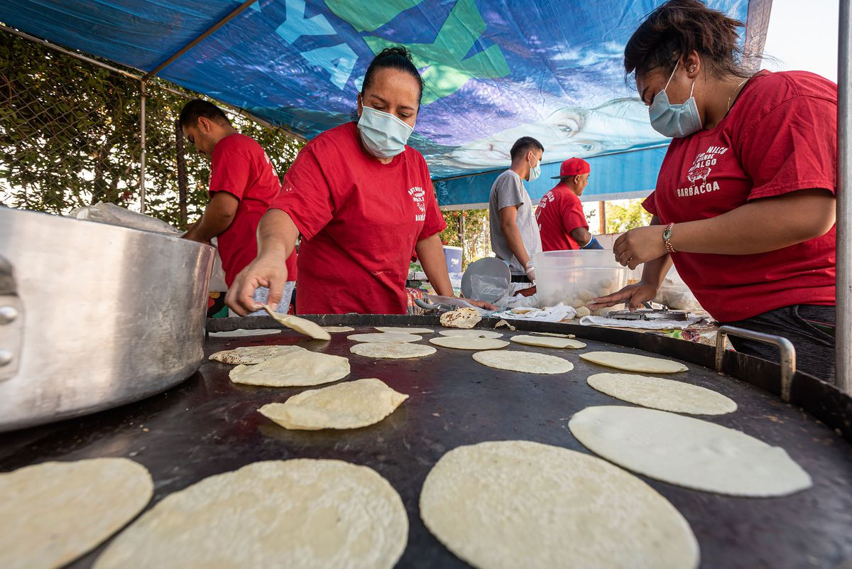 Leticia Ramirez and other family members cook tortillas on a comal.