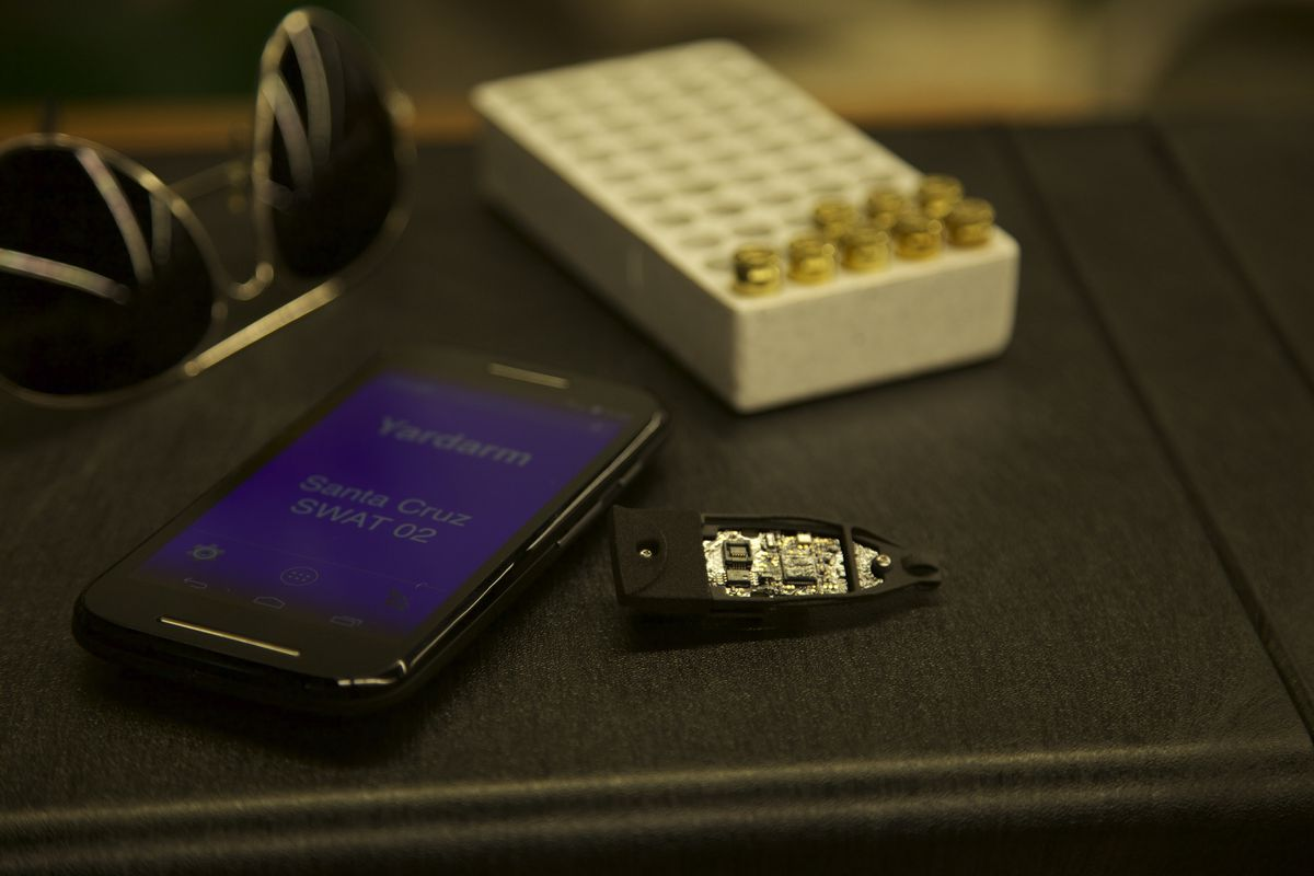 Yardarm's sensor for tracking police firearms is shown beside its smartphone app